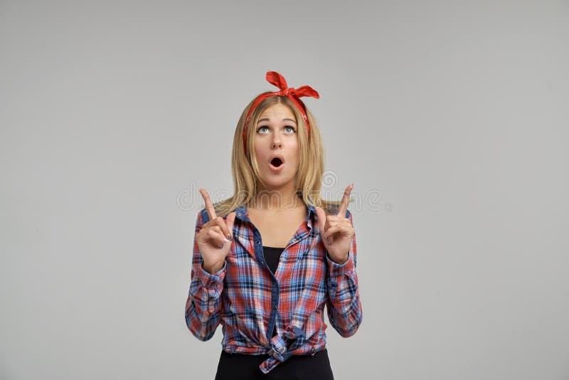 Tiro del estudio de un blonde joven lindo sorprendido abrir su boca ancha y que muestra sus dedos índices para arriba fotos de archivo