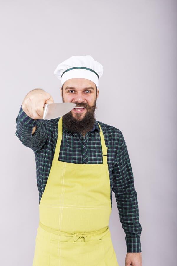 Tiro del estudio de un hombre joven barbudo con holdi del sombrero del delantal y del cocinero fotografía de archivo libre de regalías