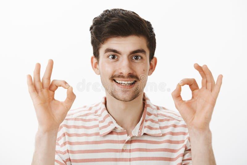 Tiro del estudio del hombre atractivo interesado satisfecho con el bigote, aumentando los fingeres y mostrando muy bien o gesto a fotografía de archivo