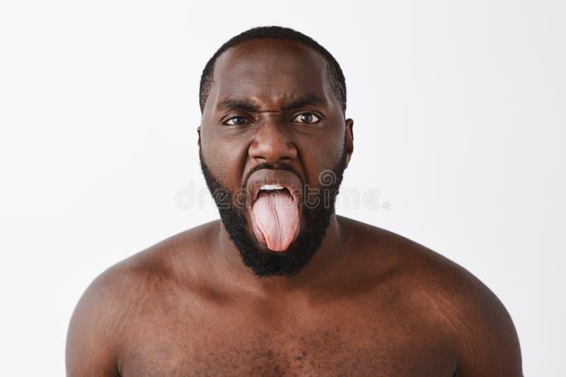 Tiro del estudio del hombre de piel morena desnudo descontentado grosero con la barba, frunciendo el ceño de la aversión y de la  fotos de archivo