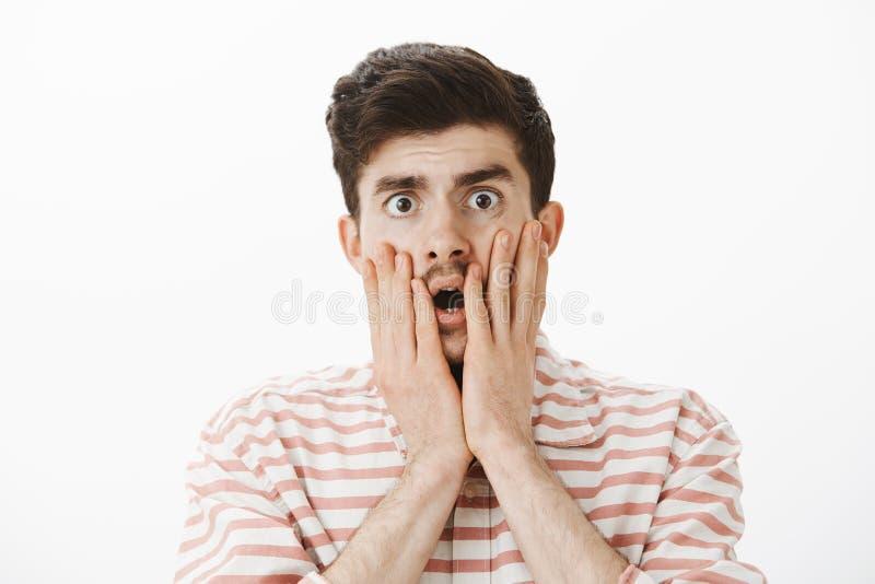 Tiro del estudio nervioso chocado y ansioso del modelo masculino hermoso con el bigote, mejillas conmovedoras con las manos, caye fotografía de archivo