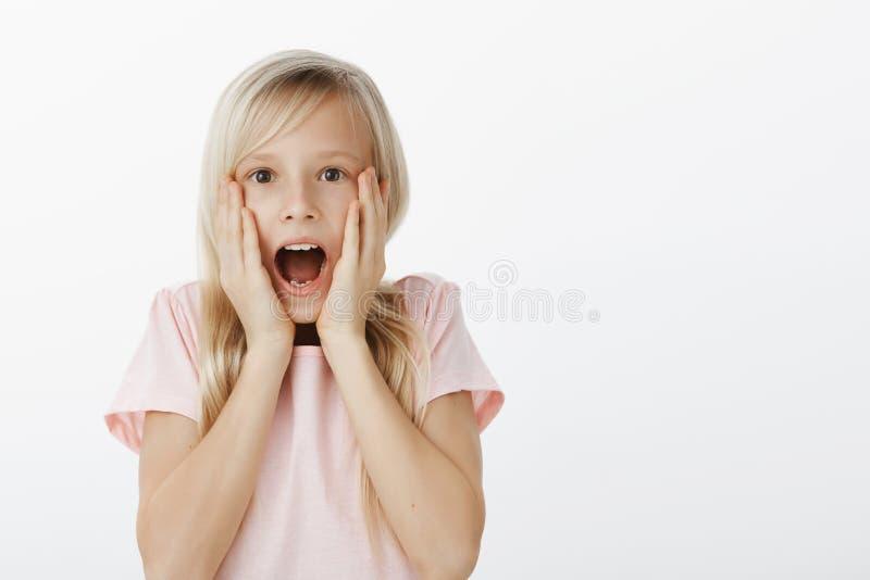 Tiro del estudio del niño femenino adorable abrumado emotivo con el pelo justo narutal, gritando de sorpresa y de emociones imagen de archivo libre de regalías