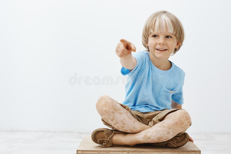 Tiro del estudio del niño rubio feliz despreocupado que es entretenido, sentándose con los pies cruzados y señalando a un lado mi foto de archivo