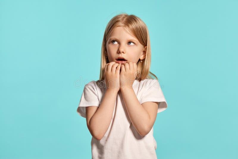 Tiro del estudio del primer de una niña rubia preciosa en una camiseta blanca que presenta contra un fondo azul fotos de archivo libres de regalías