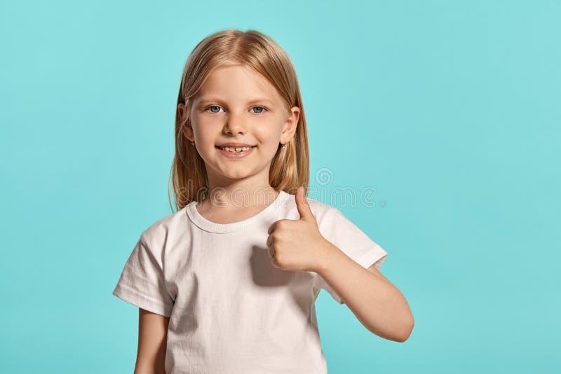 Tiro del estudio del primer de una niña rubia preciosa en una camiseta blanca que presenta contra un fondo azul foto de archivo libre de regalías