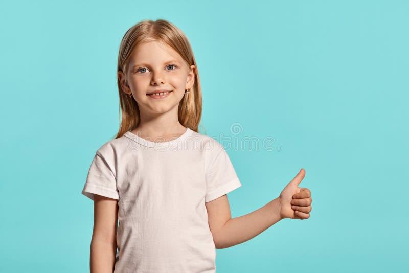 Tiro del estudio del primer de una niña rubia preciosa en una camiseta blanca que presenta contra un fondo azul imagen de archivo libre de regalías