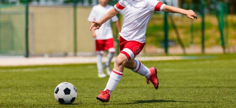 Tiro del fútbol Young Boys que golpea el partido del torneo con el pie del fútbol del fútbol en la echada de la hierba imagen de archivo libre de regalías