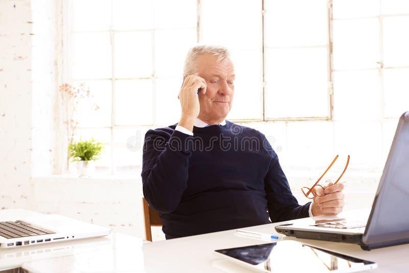 Tiro del hombre de negocios mayor que mira cuidadosamente mientras que consulta con alguien en su teléfono móvil foto de archivo libre de regalías