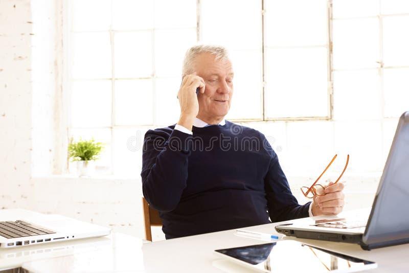 Tiro del hombre de negocios mayor que mira cuidadosamente mientras que consulta con alguien en su teléfono móvil fotografía de archivo libre de regalías