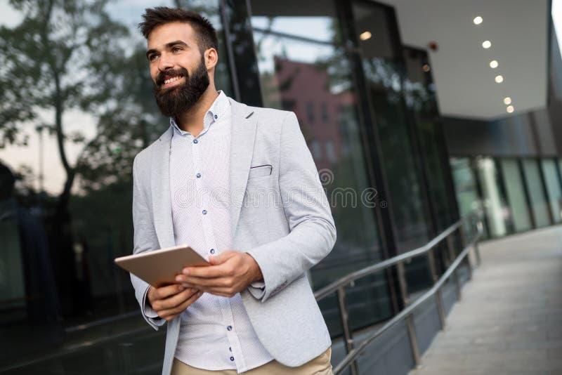 Tiro del hombre de negocios sonriente que se sienta en banco con la tableta digital fotos de archivo libres de regalías