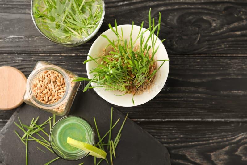 Tiro del jugo sano con la hierba y las semillas brotadas del trigo en la tabla de madera fotografía de archivo libre de regalías