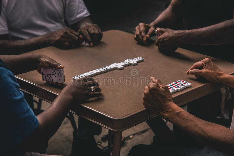Tiro del primer de cuatro personas africanas que juegan dominós alrededor de una tabla imagenes de archivo
