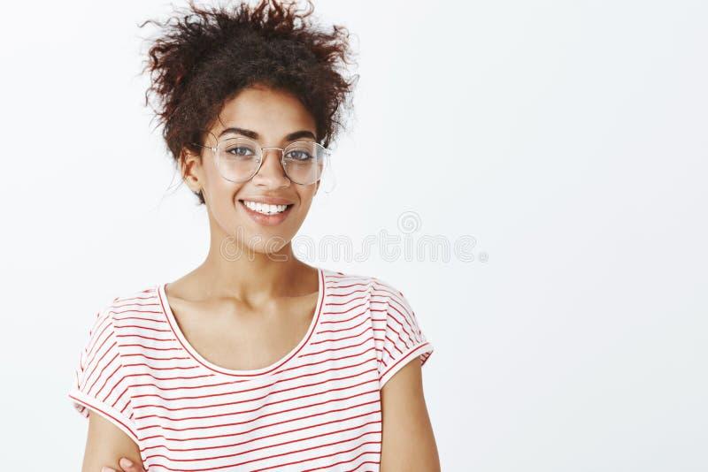 Tiro del primer de la mujer joven de amistoso-mirada confiada con el pelo rizado peinado en vidrios de moda y camiseta rayada foto de archivo