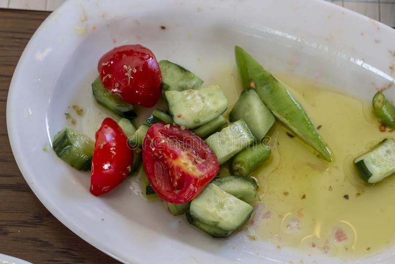 Tiro del primer del tomate y del cucmber en el aceite - placa blanca llenada imagen de archivo libre de regalías