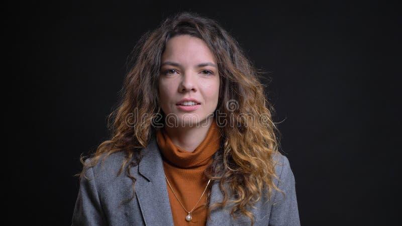 Tiro del primo piano di giovane donna di affari caucasica attraente che è premurosa e che sorride con il fondo isolato sul nero fotografia stock libera da diritti
