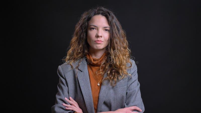 Tiro del primo piano di giovane donna di affari caucasica attraente che fa attraversare armi e che sorride con confidenza mentre  fotografia stock
