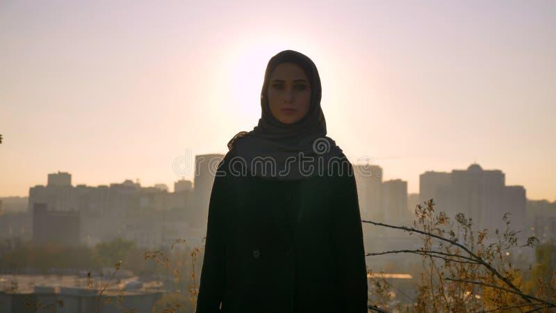 Tiro del primo piano di giovane femmina attraente nel hijab che esamina diritto la macchina fotografica con l'ambiente urbano sui fotografia stock libera da diritti