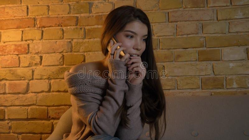 Tiro del primo piano di giovane femmina caucasica graziosa che rivolge al telefono con espressione facciale emozionante mentre ri fotografia stock