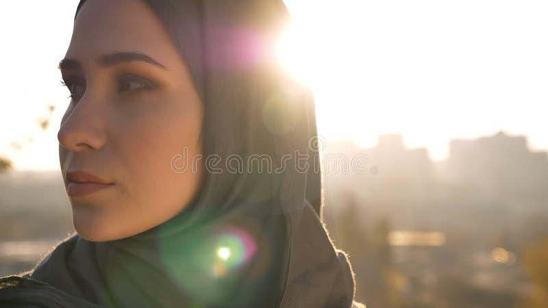Tiro del primo piano di giovane femmina musulmana attraente nel hijab che esamina il lato con l'ambiente urbano sui precedenti fotografia stock libera da diritti