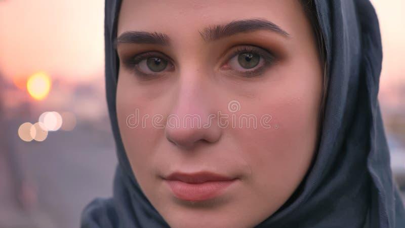 Tiro del primo piano di giovane fronte femminile attraente nel hijab che esamina diritto la macchina fotografica con la città urb immagine stock libera da diritti