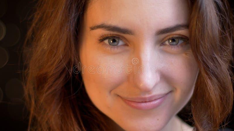 Tiro del primo piano di giovane fronte femminile caucasico attraente che sorride e che esamina diritto la macchina fotografica co fotografie stock libere da diritti