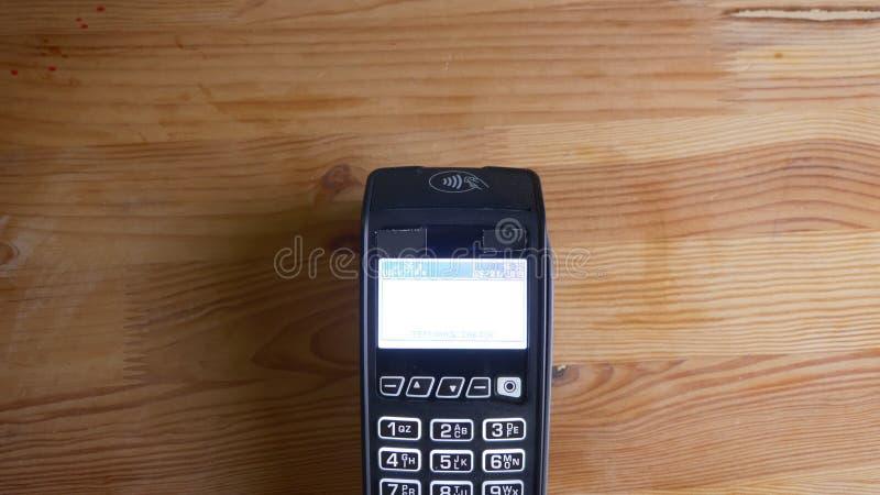 Tiro del primo piano di un terminale di pagamento che ? usato per il pagamento da un app sul telefono all'interno Mano che ? espl fotografia stock