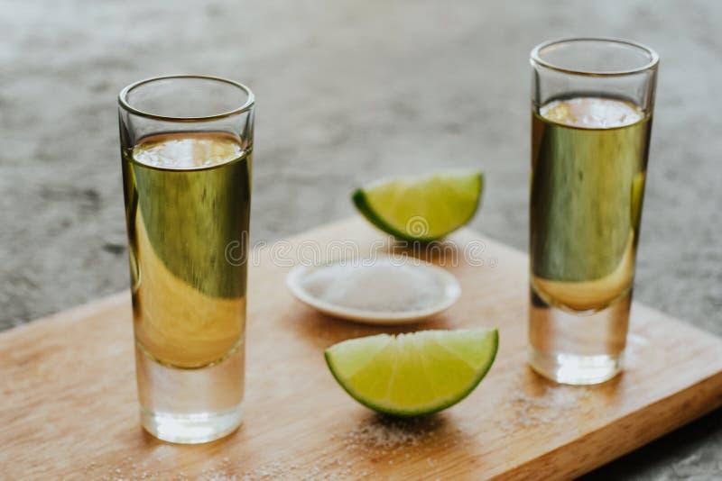Tiro del Tequila, bebidas fuertes alcohólicas mexicanas y pedazos de cal con la sal en México imagen de archivo