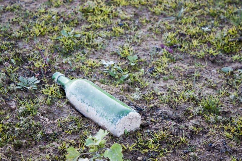 Tiro della bottiglia via in un campo fotografia stock
