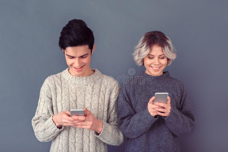 Tiro dello studio della donna e del giovane isolato sulla parete grigia che passa in rassegna media sociali immagine stock