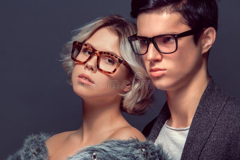 Tiro dello studio della donna e del giovane su alta moda grigia della parete fotografie stock libere da diritti