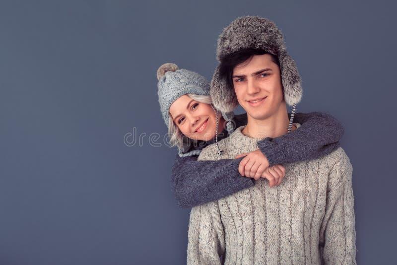 Tiro dello studio della donna e del giovane sull'abbracciare grigio della parete fotografie stock libere da diritti