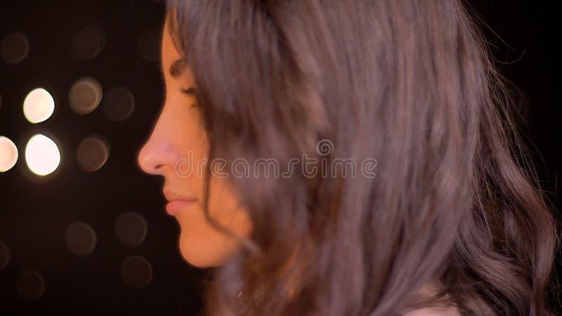 Tiro di vista laterale del primo piano di giovane fronte femminile caucasico attraente che guarda in avanti con le luci del bokeh fotografie stock