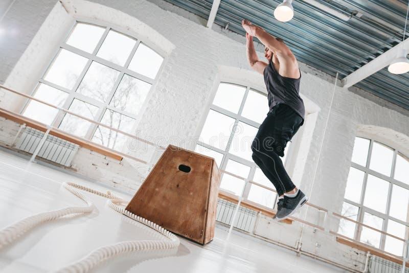 Tiro dinâmico do atleta masculino da aptidão que salta na caixa quadrada no gym do crossfit fotografia de stock royalty free