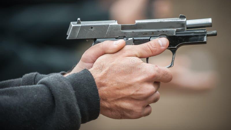 Tiro do atirador da mão esquerda e arma guardar Opinião do detalhe do close-up imagem de stock