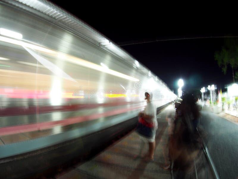 Tiro do borrão de movimento do trem movente rápido na noite com figura humana não identificada do borrão fotografia de stock