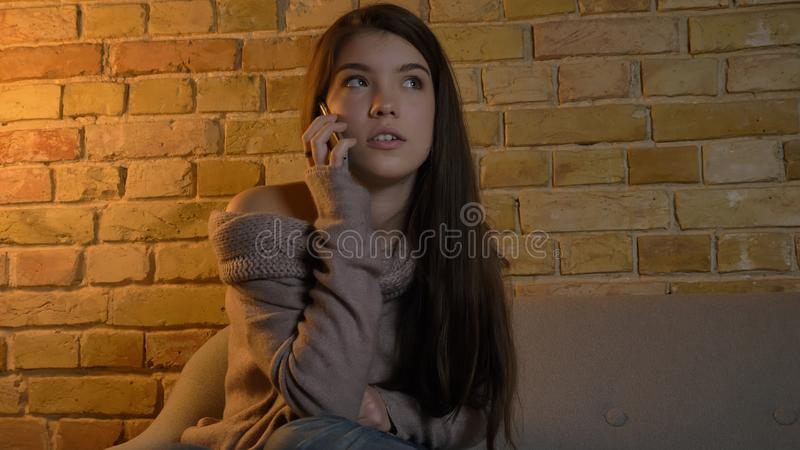 Tiro do close up da fêmea caucasiano bonita nova que tem uma conversação ocasional no telefone ao descansar no sofá na imagem de stock