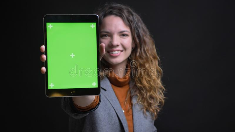 Tiro do close up da fêmea caucasiano bonita nova que usa a tabuleta e mostrando a tela verde do croma ao sorriso da câmera imagem de stock
