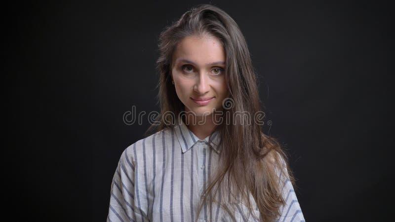 Tiro do close up da fêmea caucasiano bonito nova que olha a câmera e que sorri seductively levantando na frente da câmera fotografia de stock