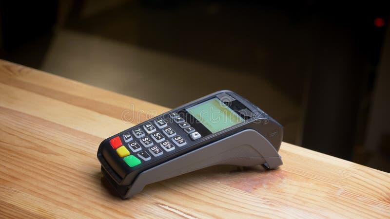 Tiro do close up de um terminal do pagamento que está sendo usado para o pagamento pelo cartão de crédito no local de trabalho foto de stock