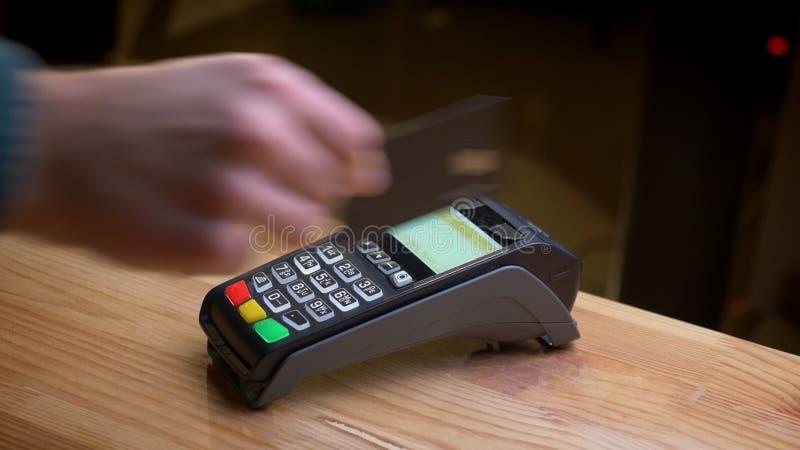 Tiro do close up de um terminal do pagamento que está sendo usado para o pagamento pelo cartão de crédito no local de trabalho fotos de stock royalty free