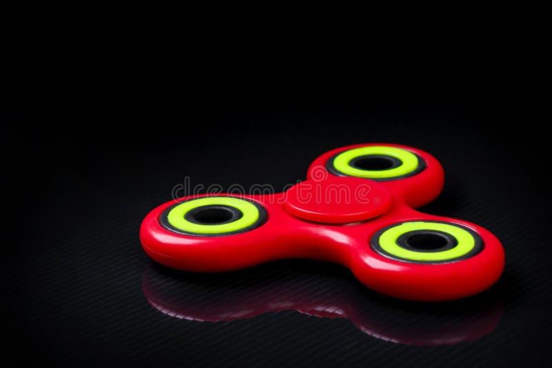 Tiro do close-up do girador vermelho-verde do dedo da inquietação no fundo preto do brilho fotografia de stock