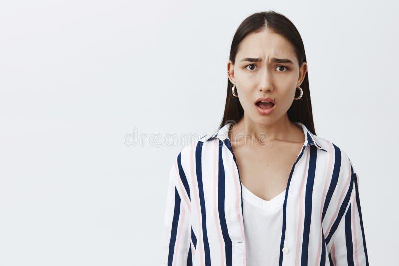 Tiro do estúdio da esposa nova atrativa desagradada chocada em blusa listrada com beleza natural, olhando de sobrancelhas franzid imagem de stock