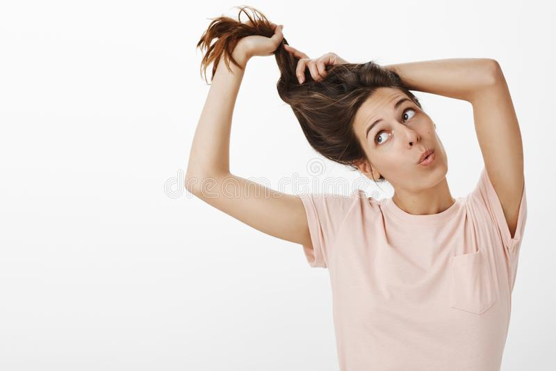 Tiro do estúdio da menina que prepara-se para a universidade que veste acima e que faz o penteado perto dos bordos de dobramento  fotografia de stock