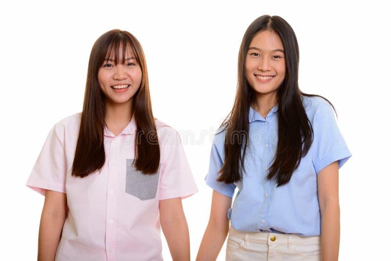 Tiro do estúdio de um sorriso asiático feliz novo de dois adolescentes imagem de stock