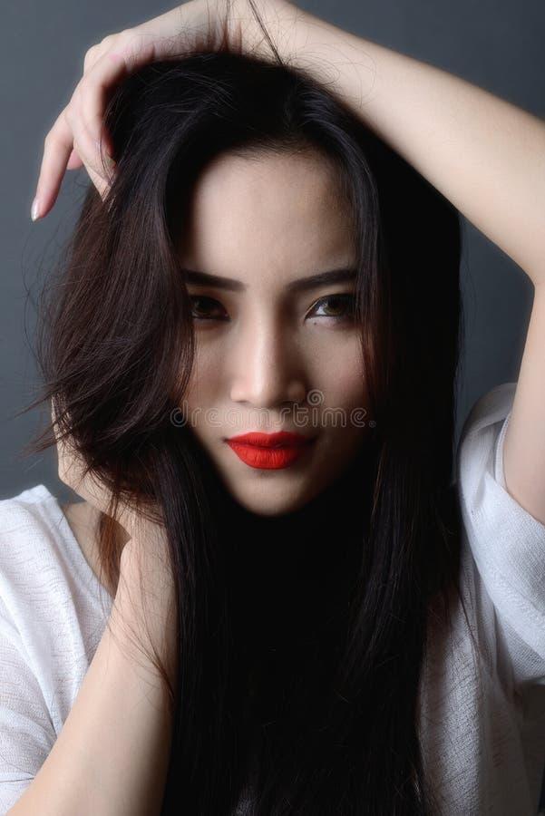 Tiro do estúdio, fim acima da cara do preto asiático bonito do modelo da mulher fotografia de stock