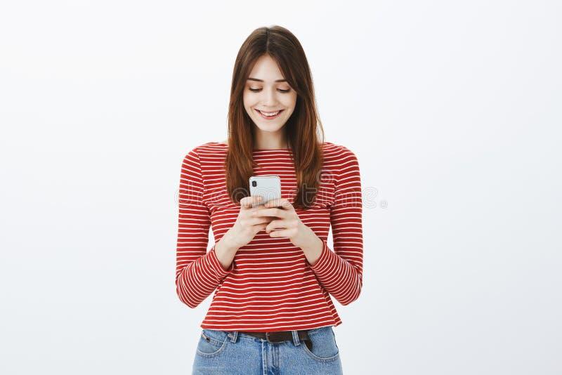 Tiro do estúdio do freelancer fêmea bonito surpreendido que faz a nomeação através do smartphone, guardando o dispositivo com amb imagem de stock