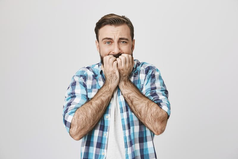 Tiro do estúdio do homem adulto sombrio na camisa verificada, sendo aturdido do medo, expressando a admiração guardando as mãos s imagem de stock