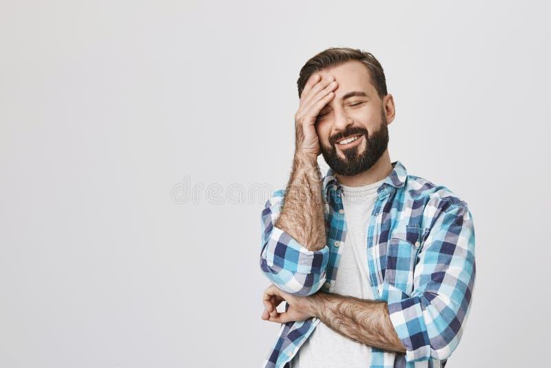 Tiro do estúdio do homem farpado considerável na camisa verificada, guardando a mão na testa ao sorrir, expressando o positivo foto de stock