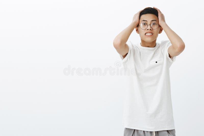 Tiro do estúdio do incomodado menino asiático considerável interessado preocupado e nervoso que pressiona as mãos para dirigir a  imagem de stock