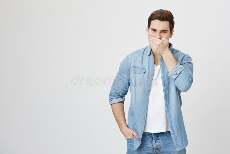 Tiro do estúdio do indivíduo novo na moda com corte de cabelo à moda que ri e que tenta escondê-lo, cobrindo a boca com a mão, es fotos de stock